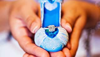 An engagement ring set atop a glittering Cinderella-inspired slipper