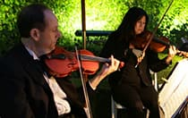 Two people playing the violin outside