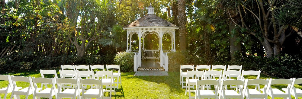 Rows of folding chairs and a gazebo on a lawn surrounded by trees