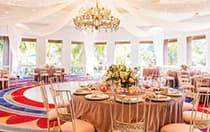 Several round tables with large floral centerpieces in a room with drapery falling from the ceiling