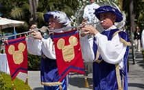 2 performers dressed in 15th century attire play trumpets with Mickey flags attached as a carriage follows behind them