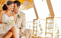 A smiling bride and groom sit together on a ship's patio