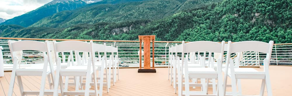 Folding chairs on the deck of ship overlooking a hillside