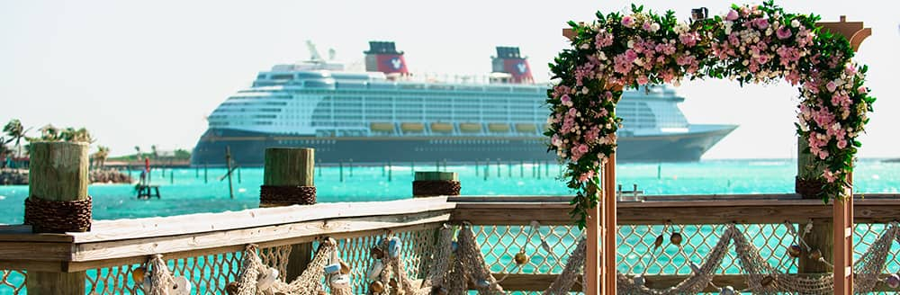 An archway covered in flowers overlooks the water and a Disney Cruise Line ship