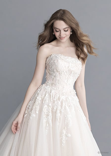 A woman stares down at the Aurora wedding gown from the 2020 Disney Fairy Tale Weddings Platinum Collection that she is wearing
