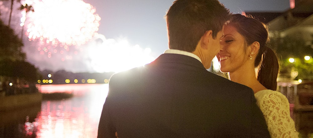A man and woman lean in for a kiss during a fireworks display