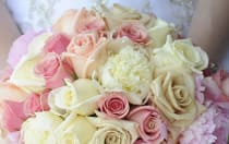A bride holds a bouquet of roses