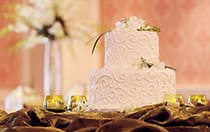 A 2 tier wedding cake on a table with several candles