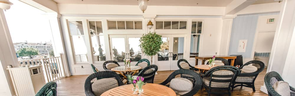 Wicker chairs surround small circular tables on a patio