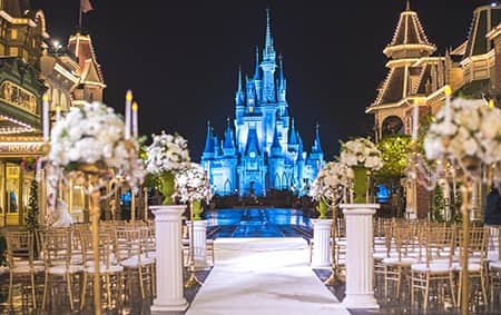 Rows of chairs and flowers arranged for a wedding ceremony with a castle as the backdrop