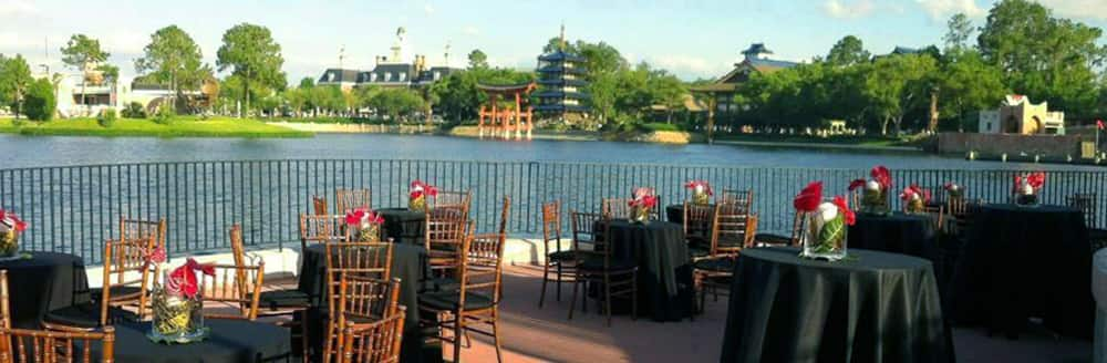 Small round tables arranged near the water with views of World Showcase
