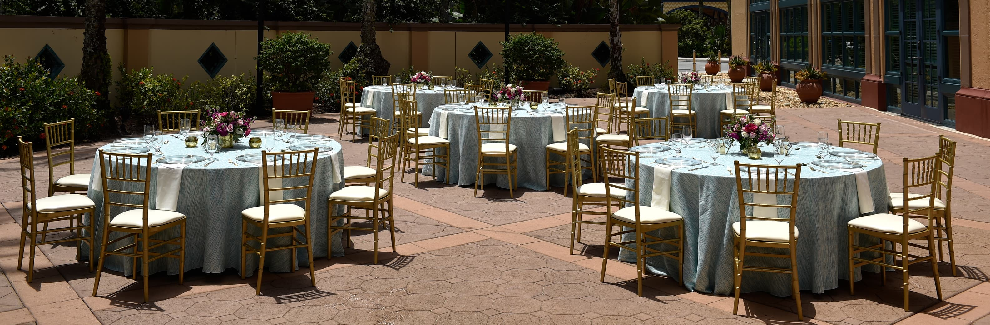 Five circular tables with chairs arranged in a courtyard surrounded by plants