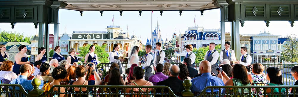 A bride and groom get married in front of a crowd of people in the train station overlooking Cinderella Castle