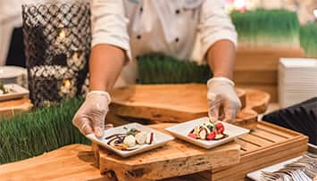 A chef places 2 small square plates on a wooden table