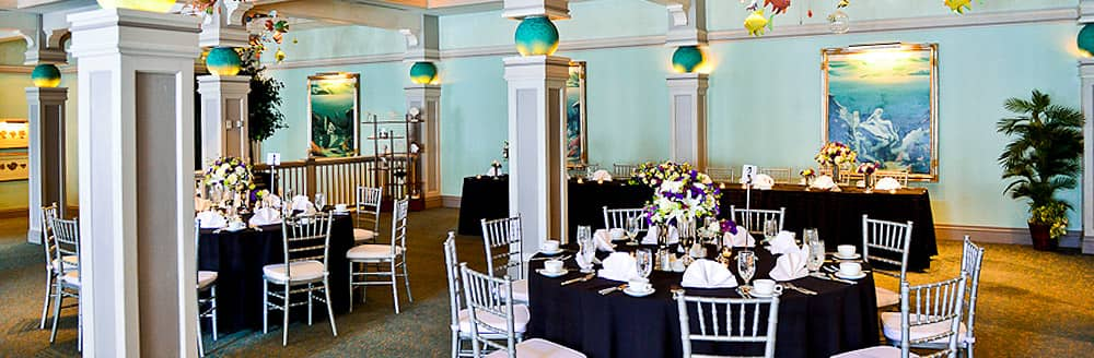An indoor venue with framed pictures of ocean inspired art, chairs and tables topped with floral centerpieces, plates, glasses and napkins