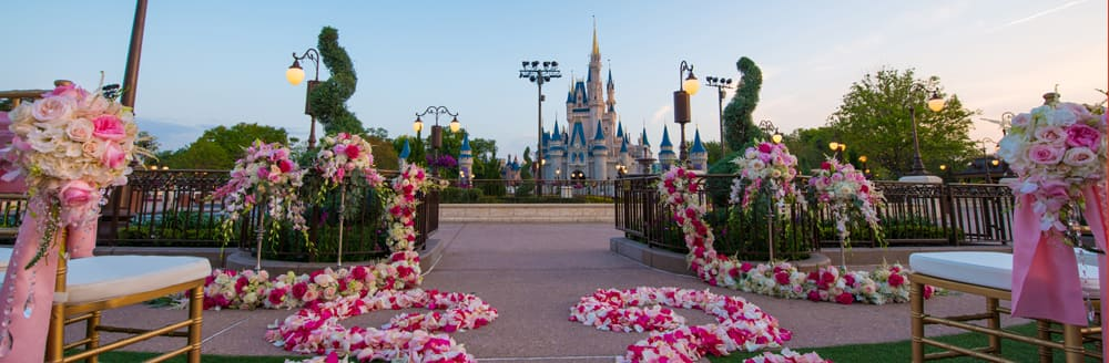 Cinderella's Castle stands in the background of an outdoor wedding venue set with chairs and floral arrangements