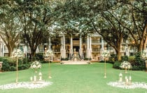 A stately manor with oak trees and a fountain is set up for an outdoor wedding on the lawn