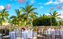 On a patio, paper lanterns are strung above tables set with floral centerpieces