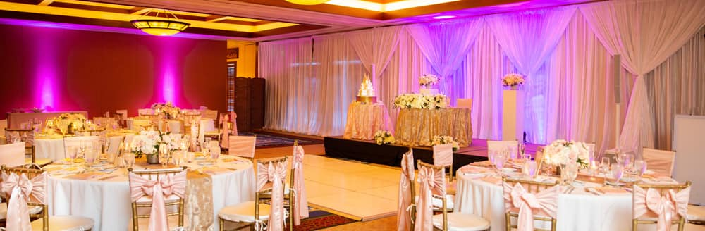 A dance floor in the middle of a reception hall holding several round tables and a cake table