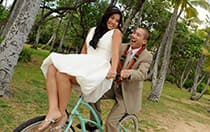 A bride sits on the handlebars while the groom pedals a bike