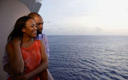 A man and a woman embrace as they enjoy the ocean scenery from their verandah