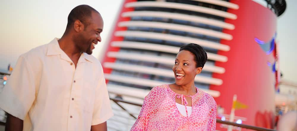 A man and a woman smile in front of the funnel of their Disney Cruise Ship