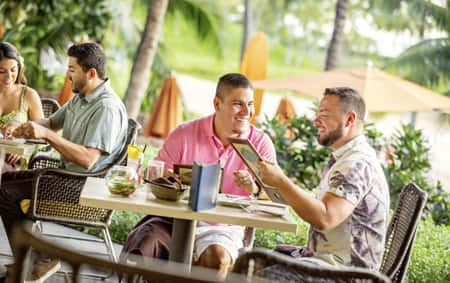 Two men check out the menu over a meal at Aulani A Disney Resort & Spa
