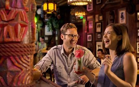 A man and a woman share a laugh at Trader Sam's Enchanted Tiki Bar