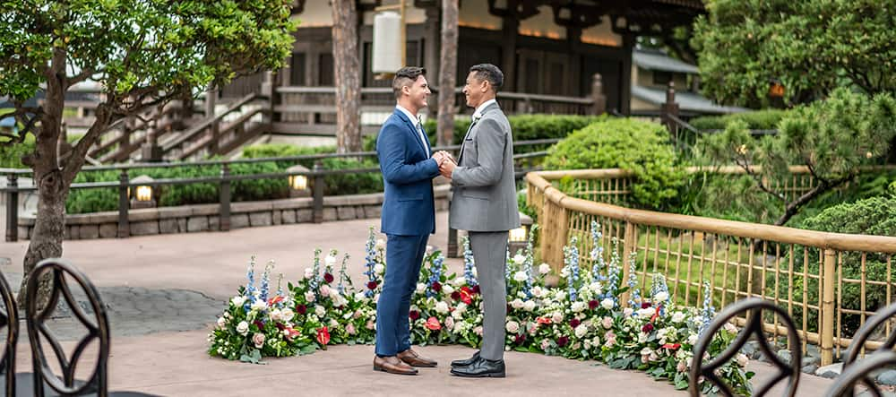 Two men are all smiles as they hold hands and look into each other's eyes near a bamboo fence in the EPCOT Japan Pavilion at Walt Disney World Resort
