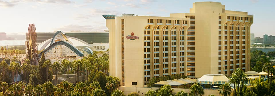 A tall building near theme park attractions with a sign that reads Disney's Paradise Pier Hotel