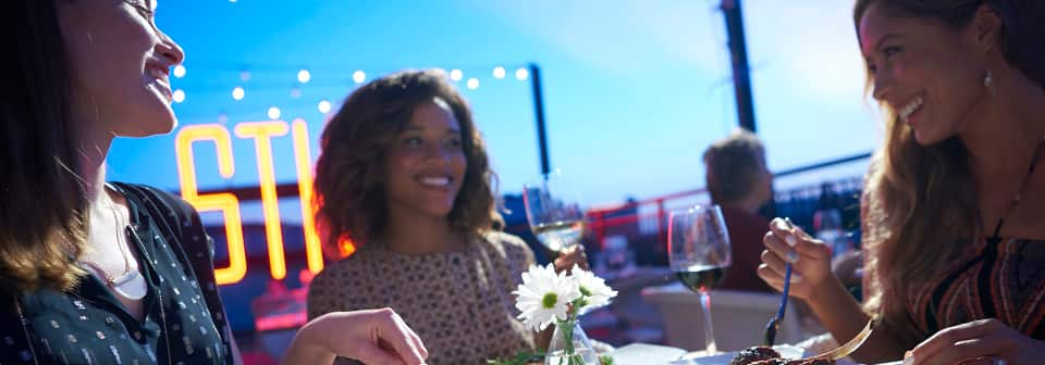 3 women smile, eat and drink at a restaurant table