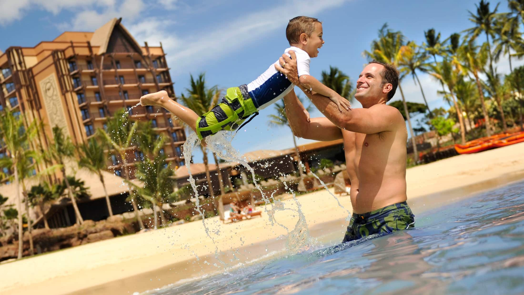 A father and son playing in the beach lagoon at Aulani Resort