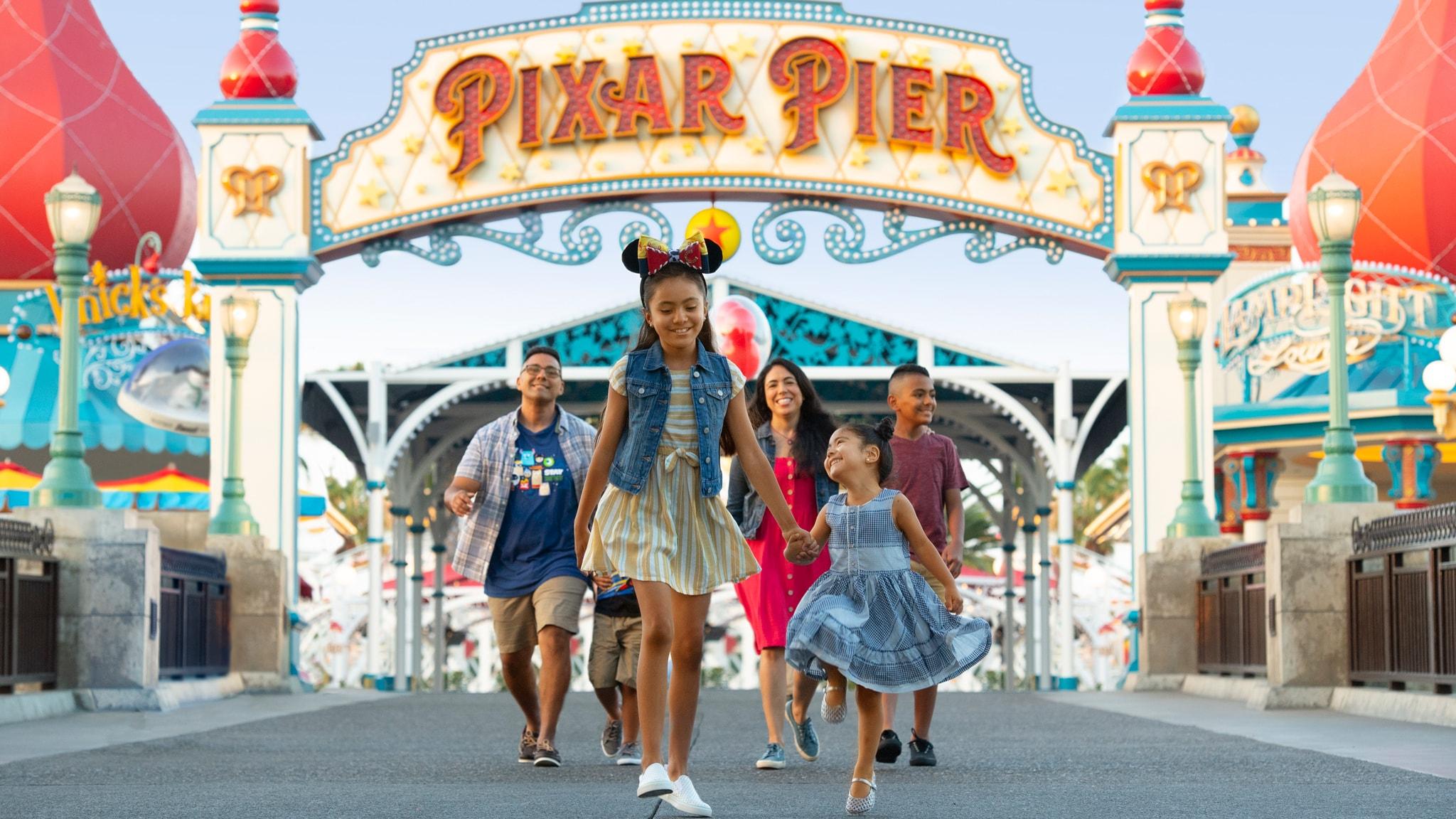 A family of six strolls under the Pixar Pier archway at Disney California Adventure Park