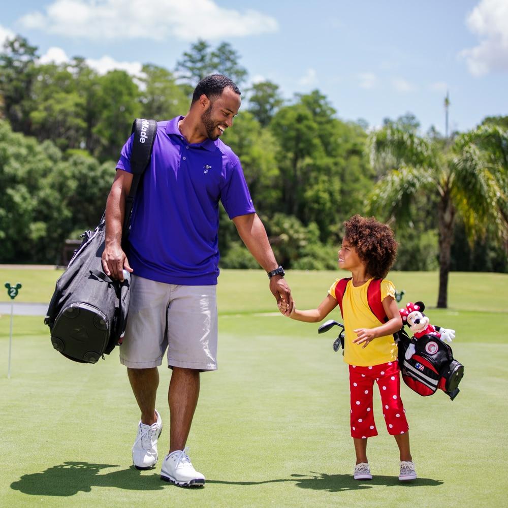 ゴルフバッグを持ち、手を繋ぎながらゴルフコースを歩く父と娘
