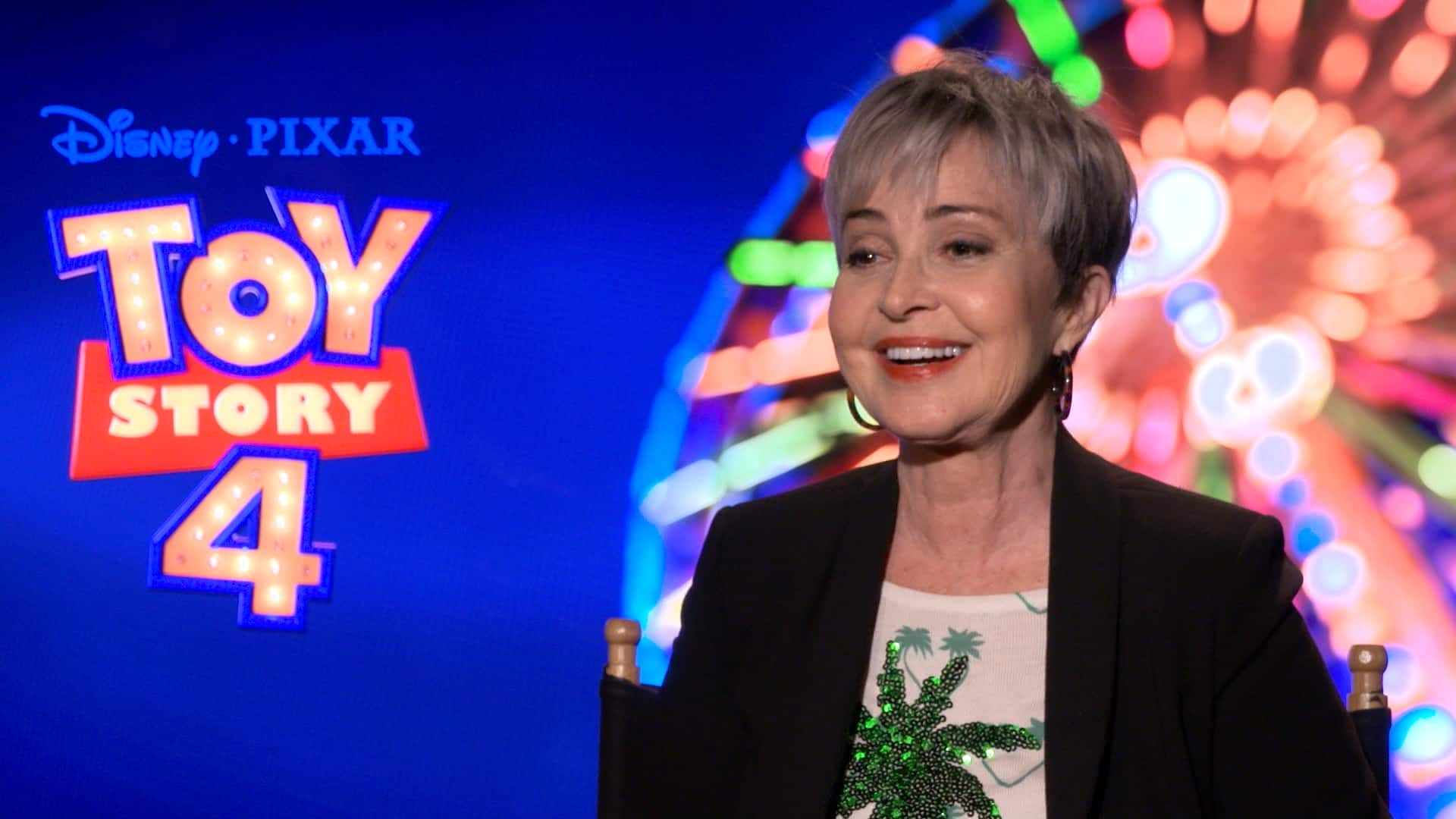 Actress Annie Potts sits in front of a promotional poster for Toy Story 4