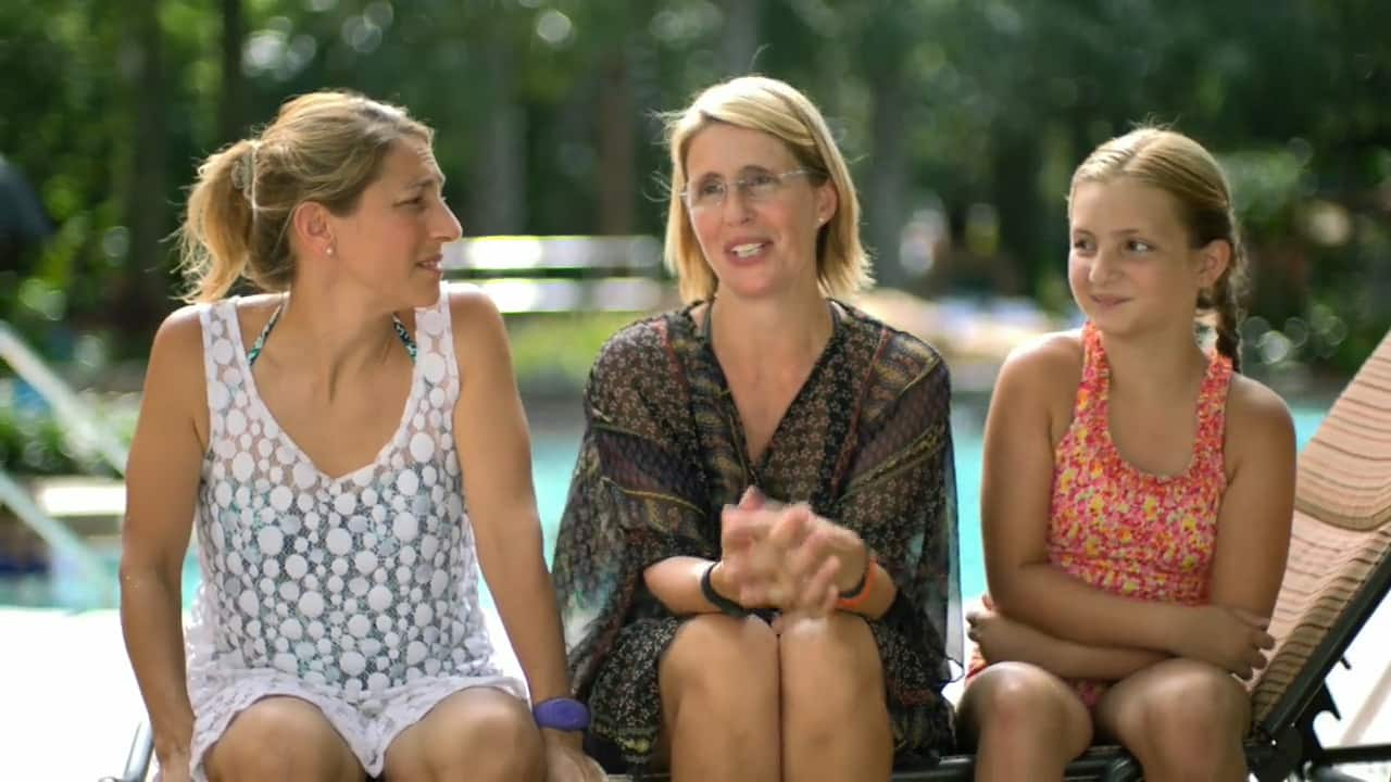 A girl and 2 women dressed in pool attire sit on a lounge chair in front of a pool