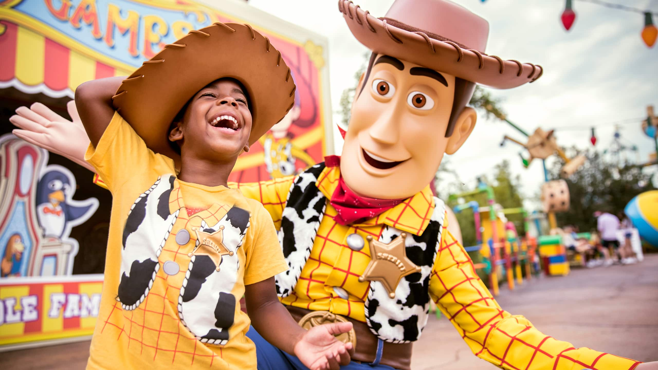 A young boy wearing a Woody themed tee shirt and cowboy hat laughs as a interacts with Woody inside of Toy Story Land