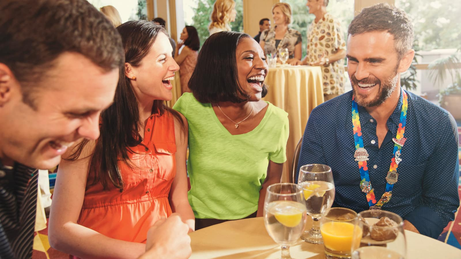 2 men and 2 women laugh as they gather around a table with 4 beverages