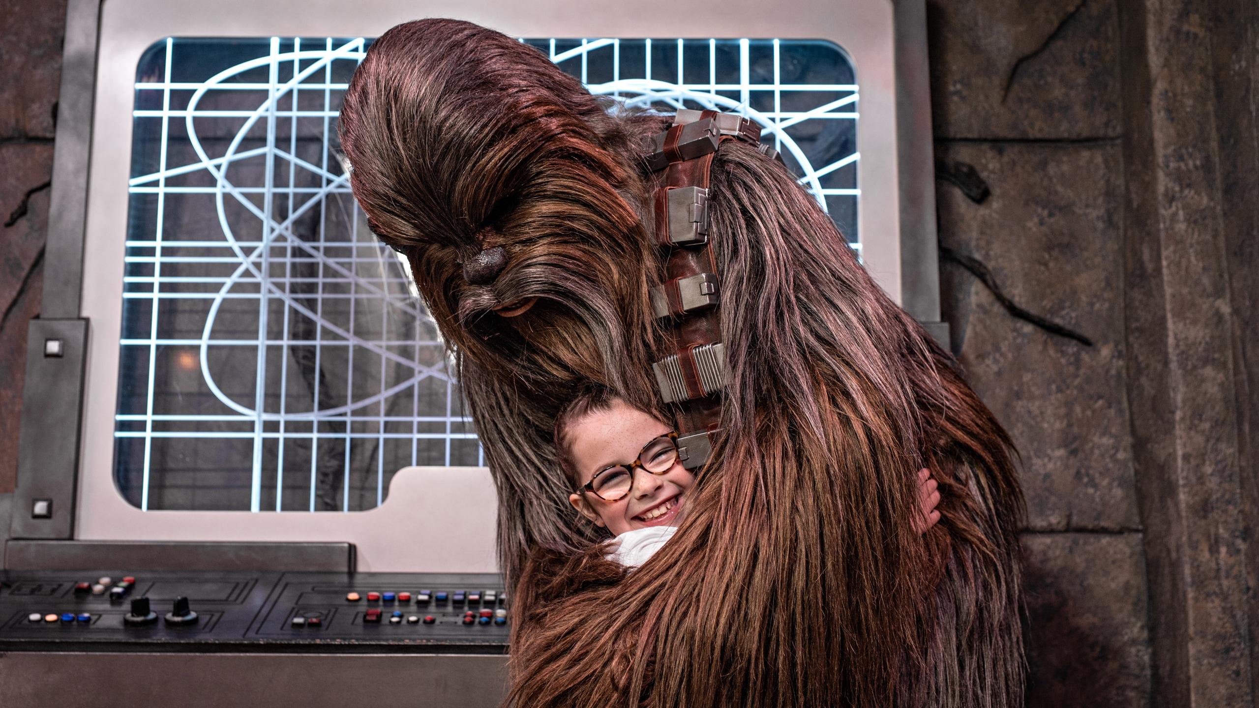 Chewbacca hugs a young girl in Star Wars Launch Bay