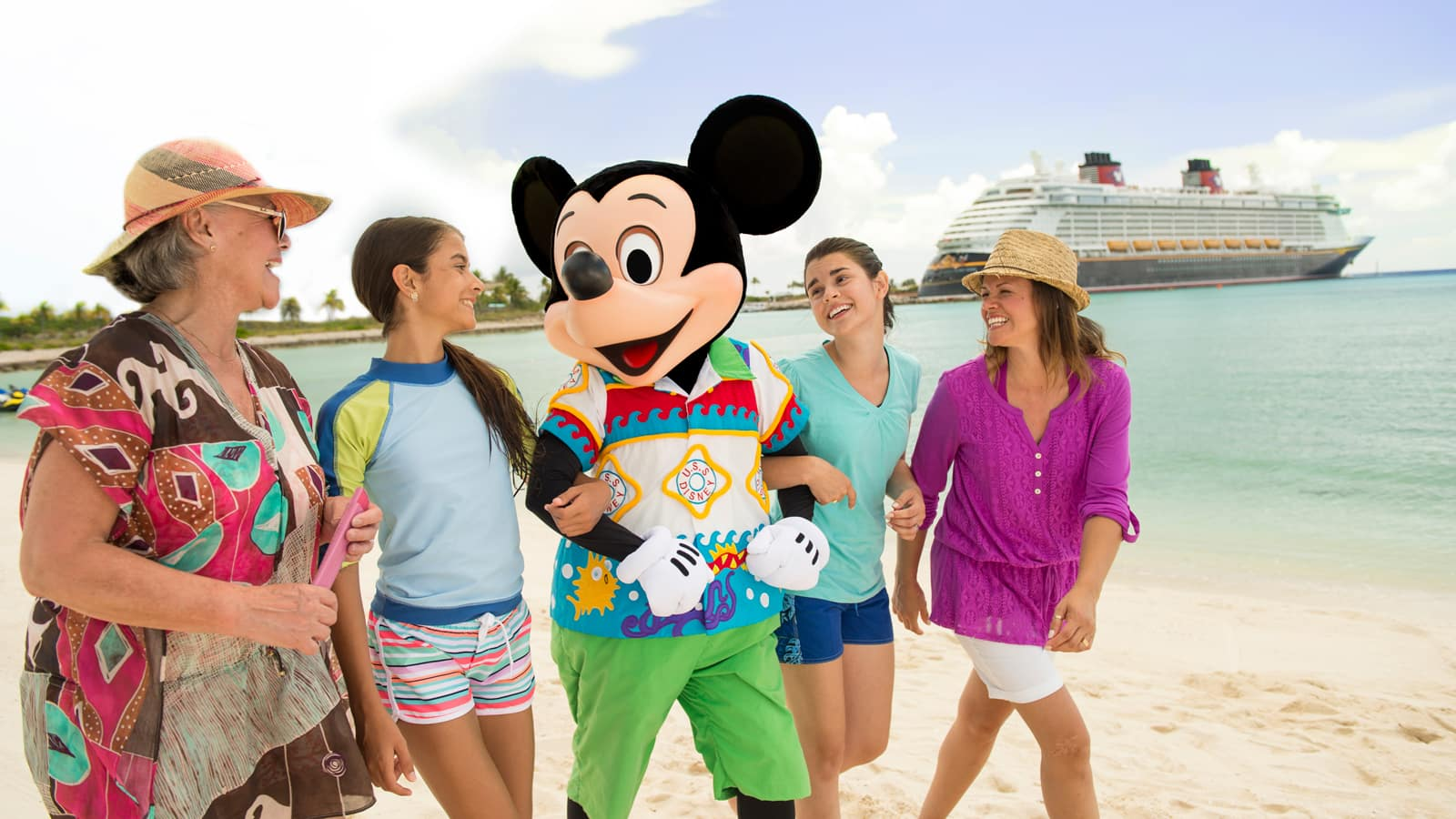 Mickey Mouse walks with 4 women on a beach with a Disney Cruise Line ship in the background