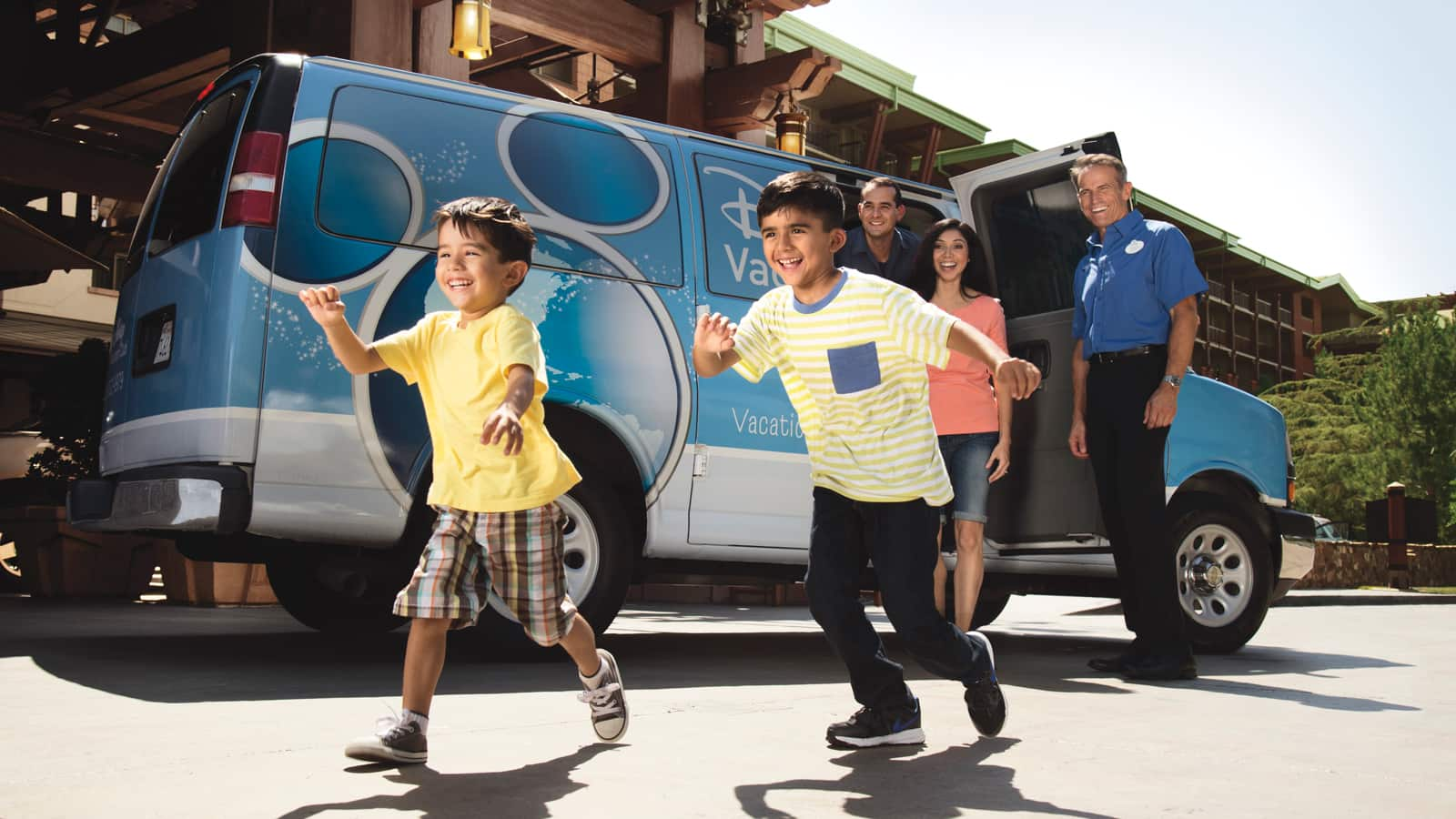 2 boys, a man and woman exit from a Disney Vacation Club van in front of a hotel