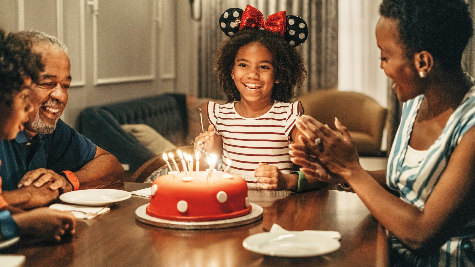 A family celebrates as a girl prepares to blow out candles on a Minnie Mouse themed cake