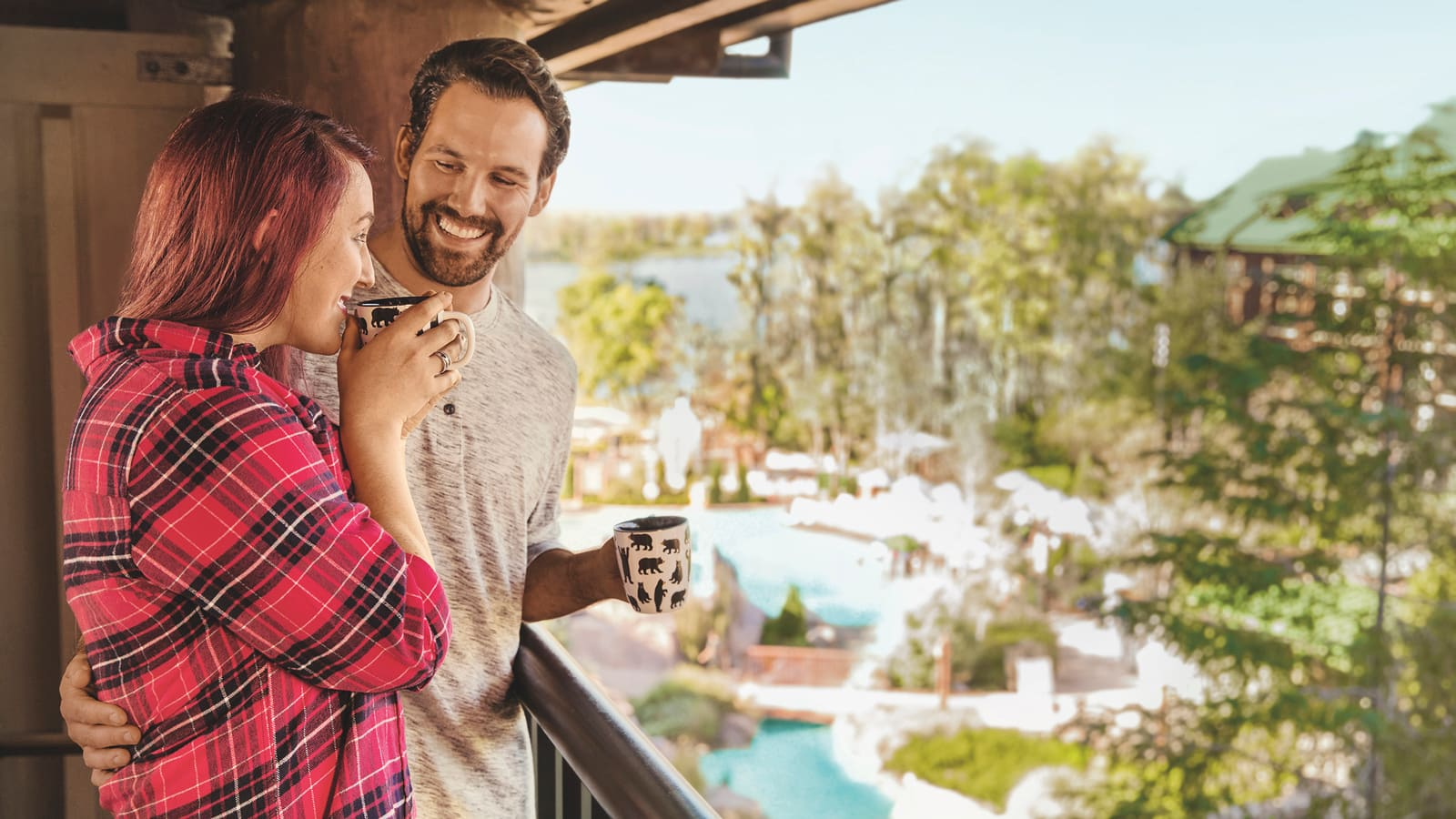 A man and woman sipping coffee while standing on the balcony of their Resort villa