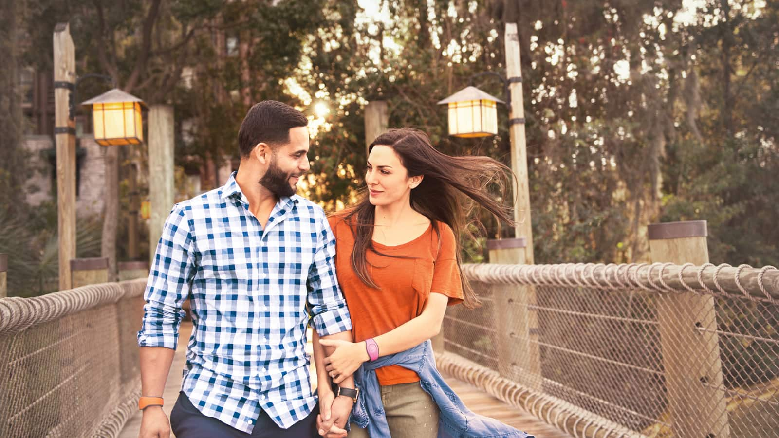 A man and woman holding hands while walking across a bridge