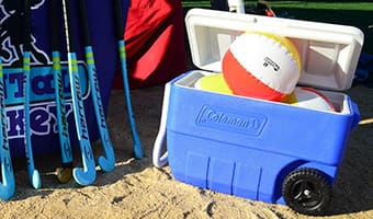 Six field hockey sticks standing next to a cooler holding 3 beach balls