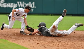 A baseball player slides into a base while his opponent reaches to tag him out