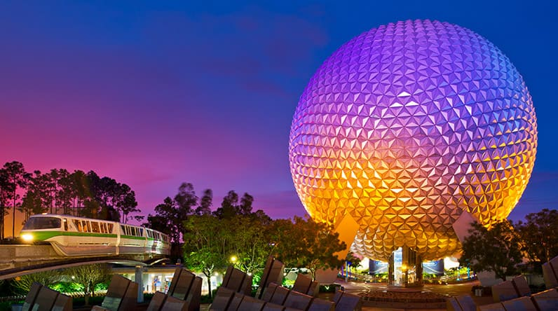 A monorail train gliding past megaliths and Spaceship Earth at night