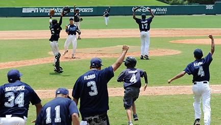 Varios jugadores de béisbol en el campo, con los brazos levantados en celebración