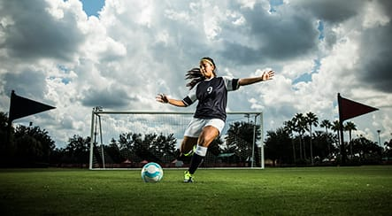 A teenage girl soccer player kicking a ball