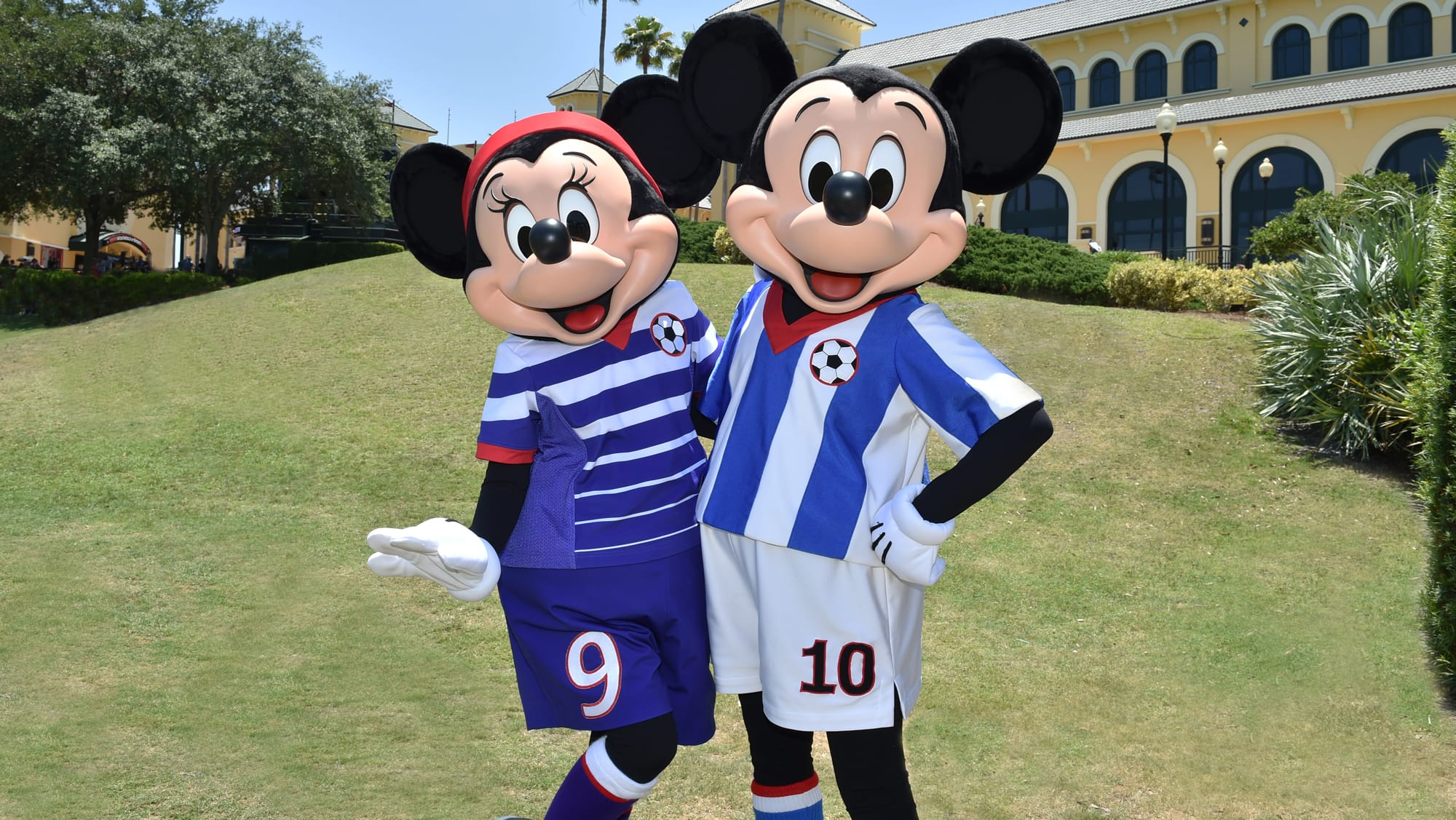 Minnie Mouse and Mickey Mouse pose in soccer uniforms on the grass at ESPN Wide World of Sports Complex